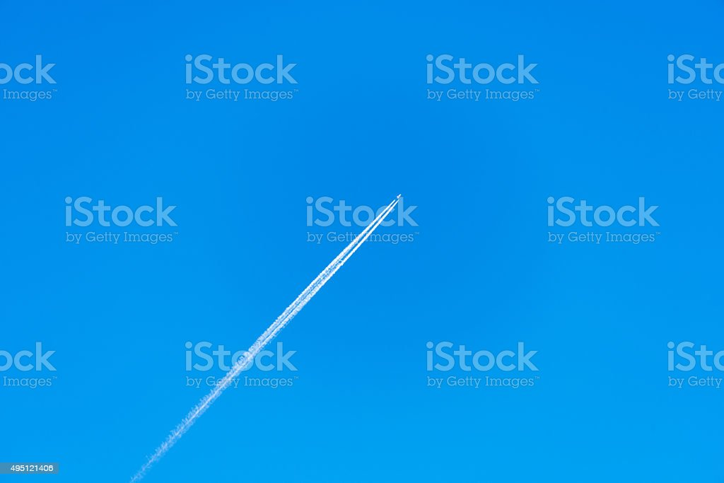 Passenger jet plane with a long trail on blue sky stock photo