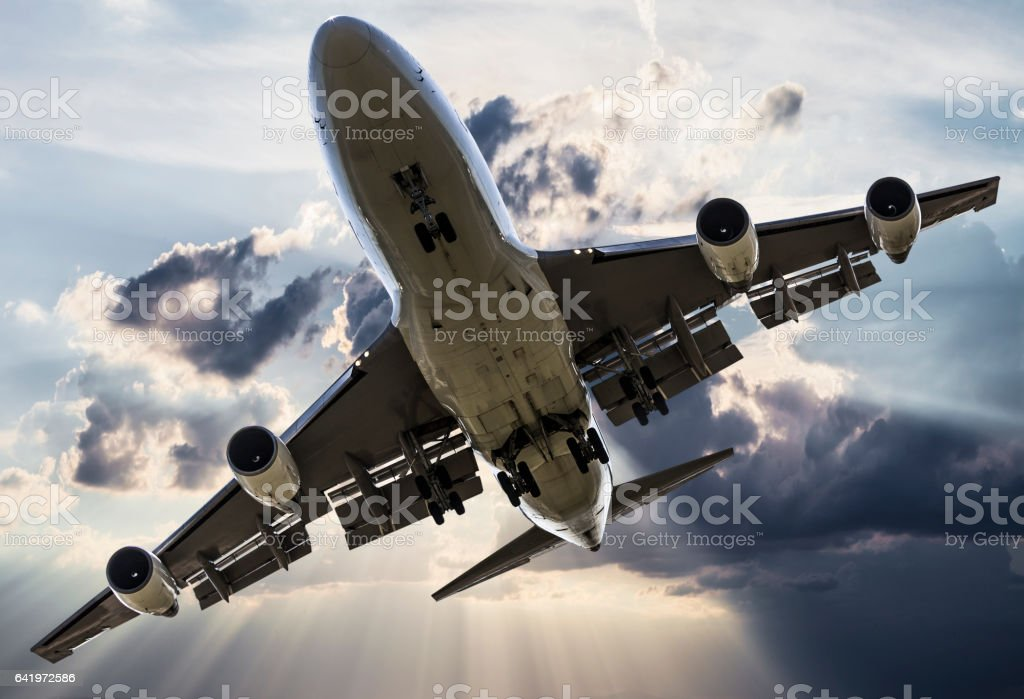 Passenger jombo jet over clouds stock photo