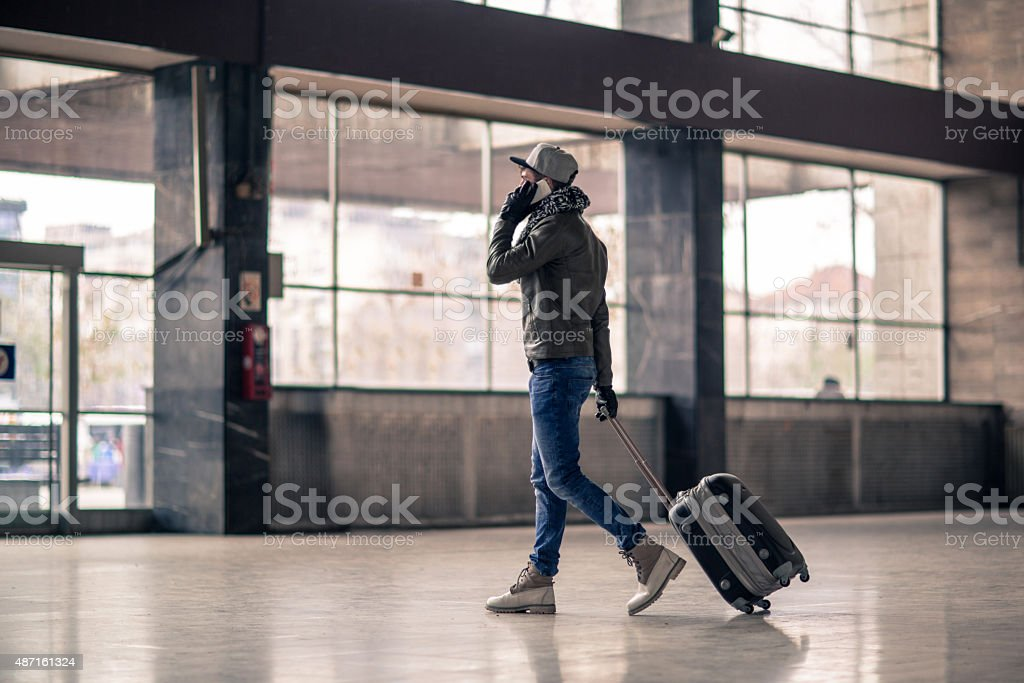 Passenger leaving the station and talking on mobile phone. stock photo