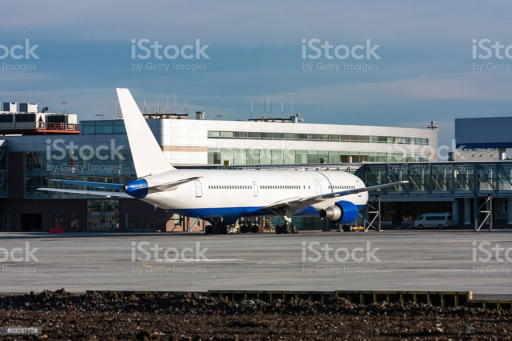 Passenger plane in the parking lot near the airport terminal building royalty-free stock photo