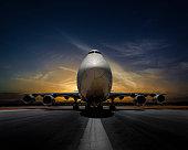 Passenger plane on runway at sunset