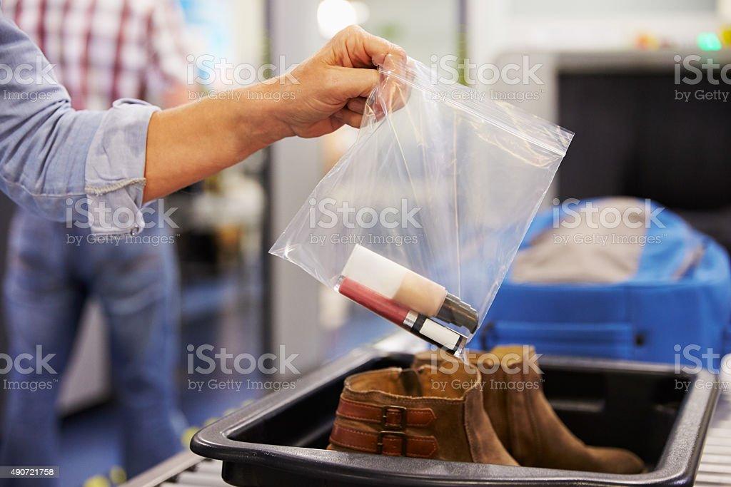 Passenger Puts Liquids Into Bag At Airport Security Check stock photo