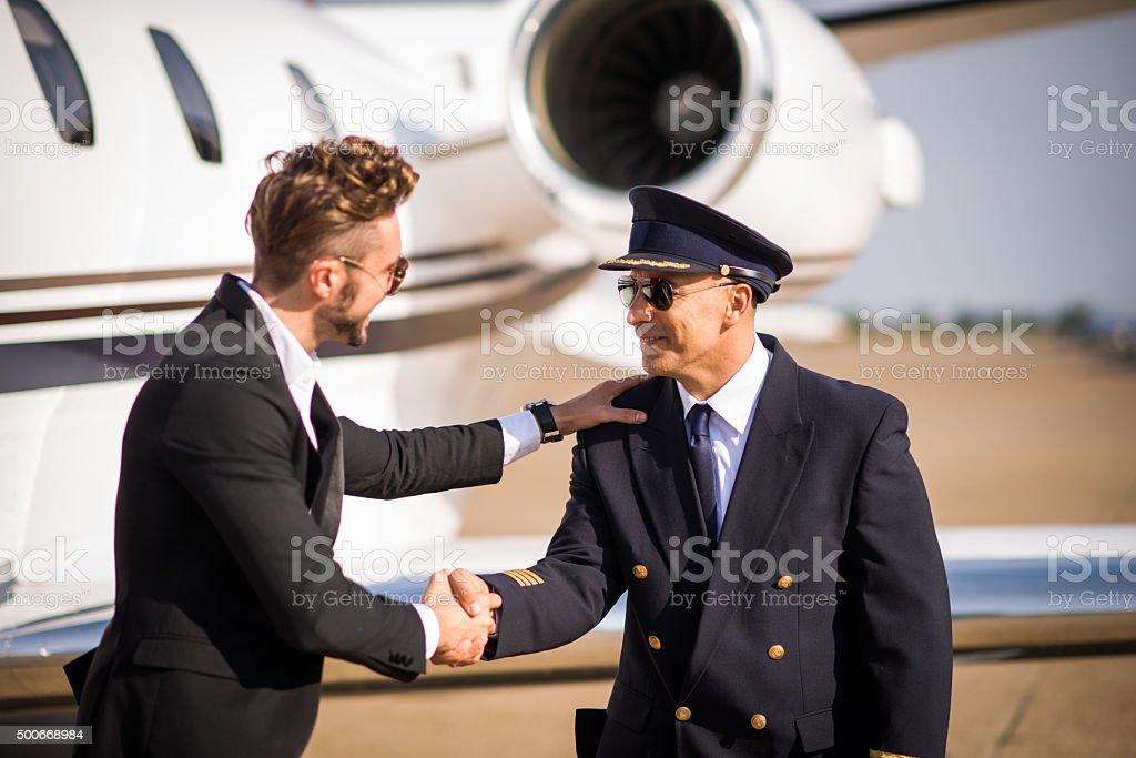 Passenger shaking hands with pilot stock photo