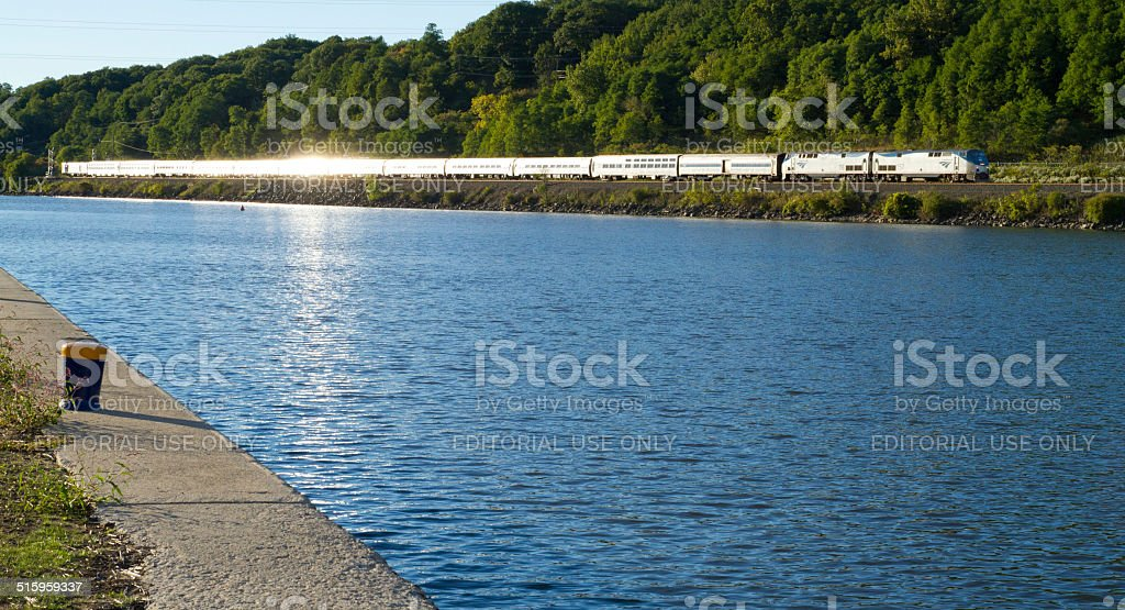 Passenger train along river with sun reflection on water stock photo
