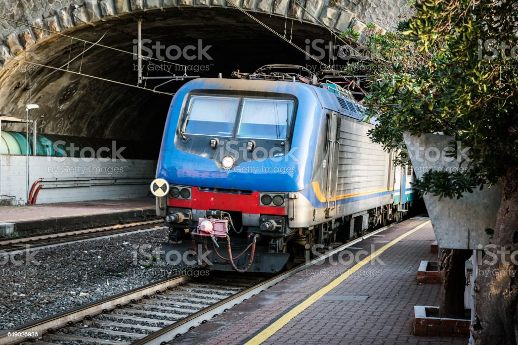 Passenger train driving out from tunnel stock photo