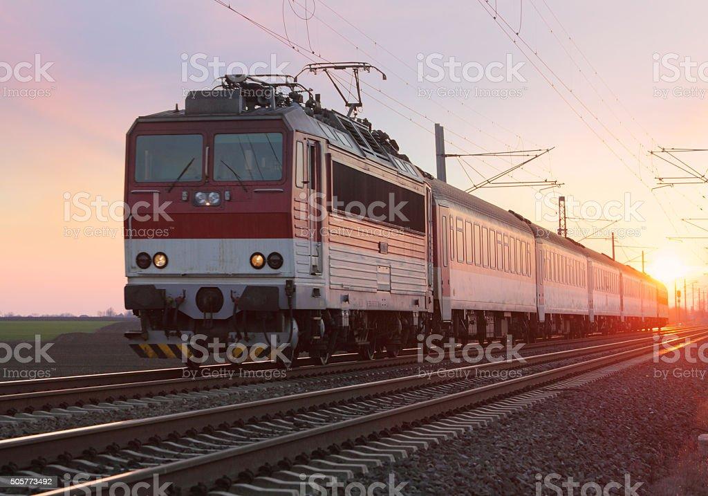Passenger train on railway at sunset stock photo