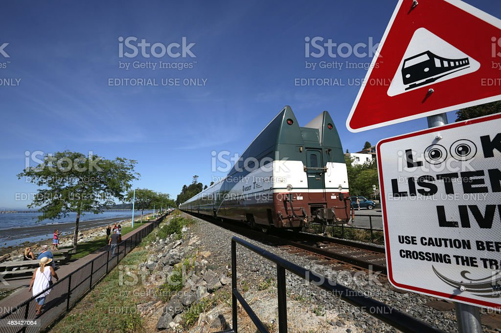 Passenger Train Travels Through White Rock, British Columbia in Summer stock photo