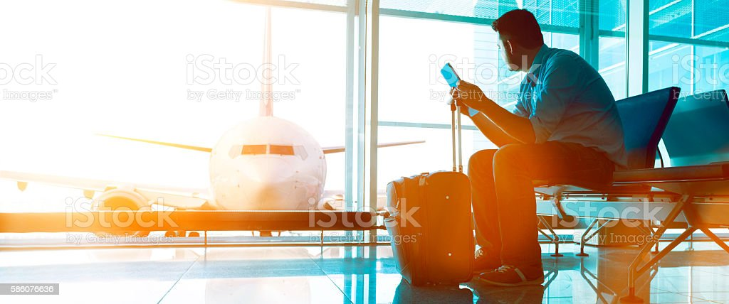Passenger waits in airport lounge for boarding call to plane stock photo