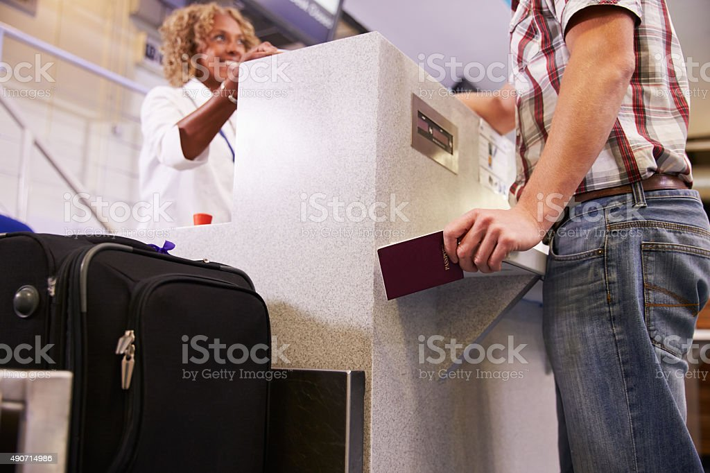Passenger Weighing Luggage At Airport Check In stock photo
