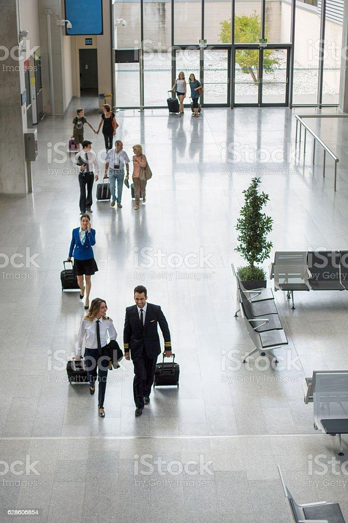 Passengers and crew walking through airport stock photo