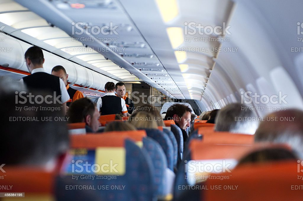 Passengers and flight attendents on a plane stock photo