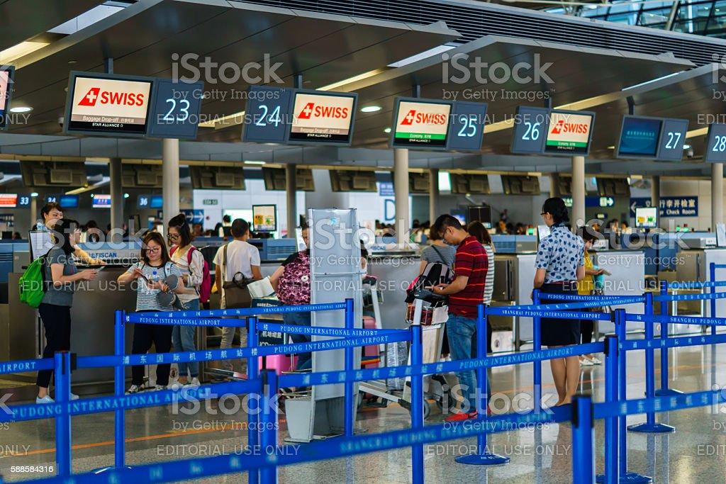 Passengers at check-in counter at Shanghai Pudong International Airport, China. stock photo