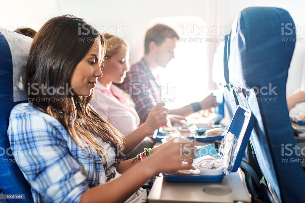 Passengers having lunch while traveling by airplane. stock photo