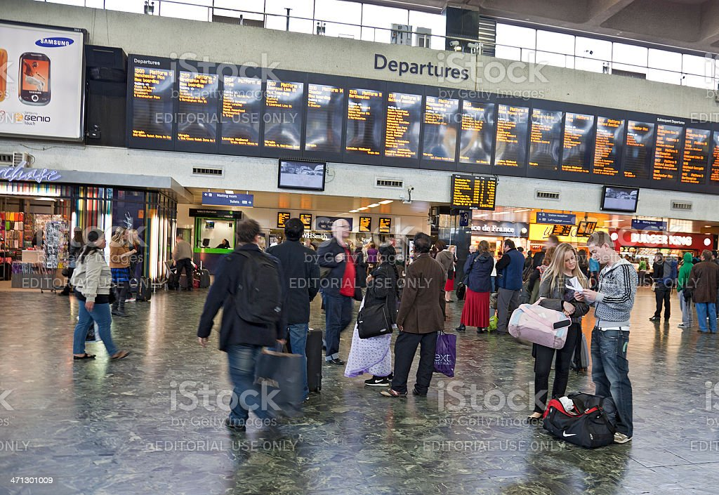Passengers in Euston station, London; Departures board royalty-free stock photo