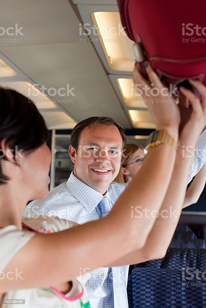 Passengers putting luggage in lockers on plane stock photo