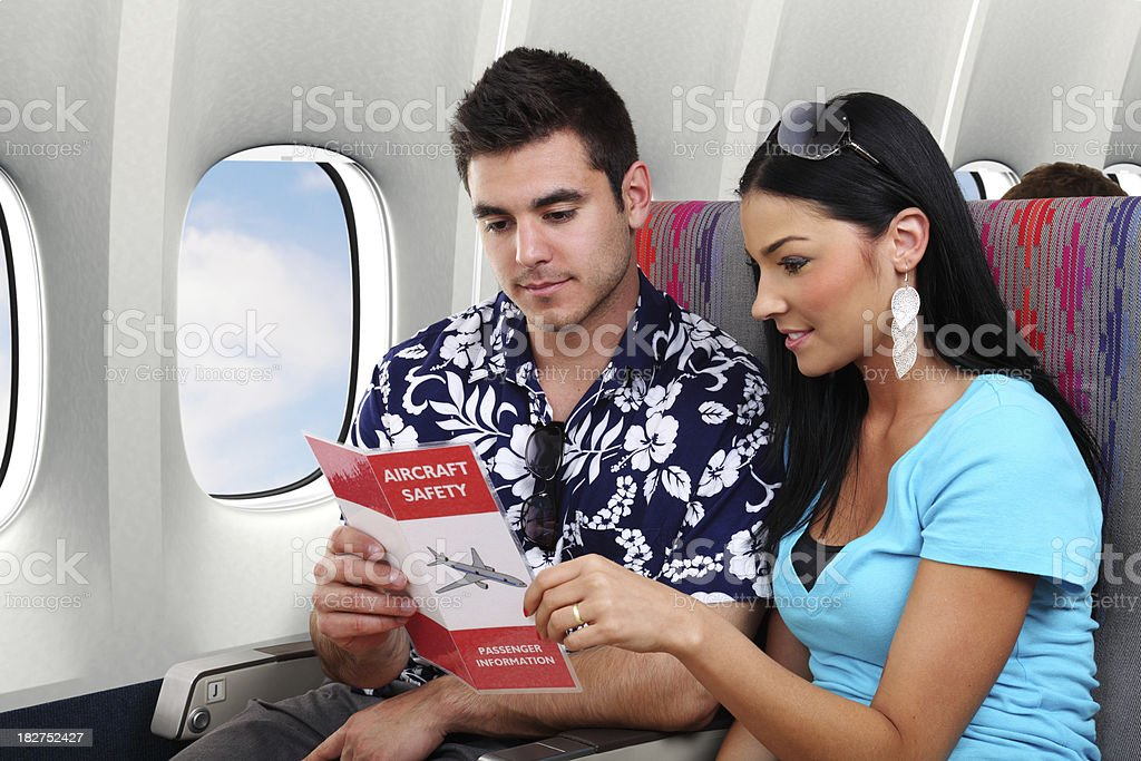 Passengers Reviewing An Airplane Safety Card royalty-free stock photo