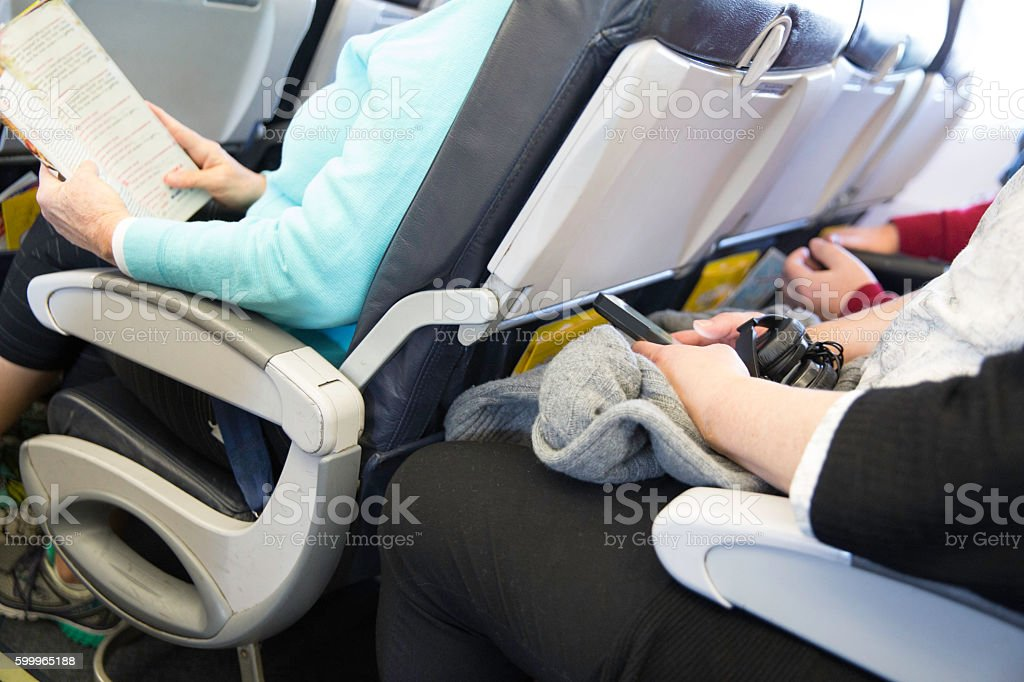 Passengers seated on an airplane are cramped in their seats stock photo