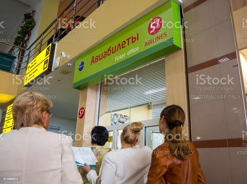 Passengers stand in line at airline ticket counter S7 Airlines stock photo