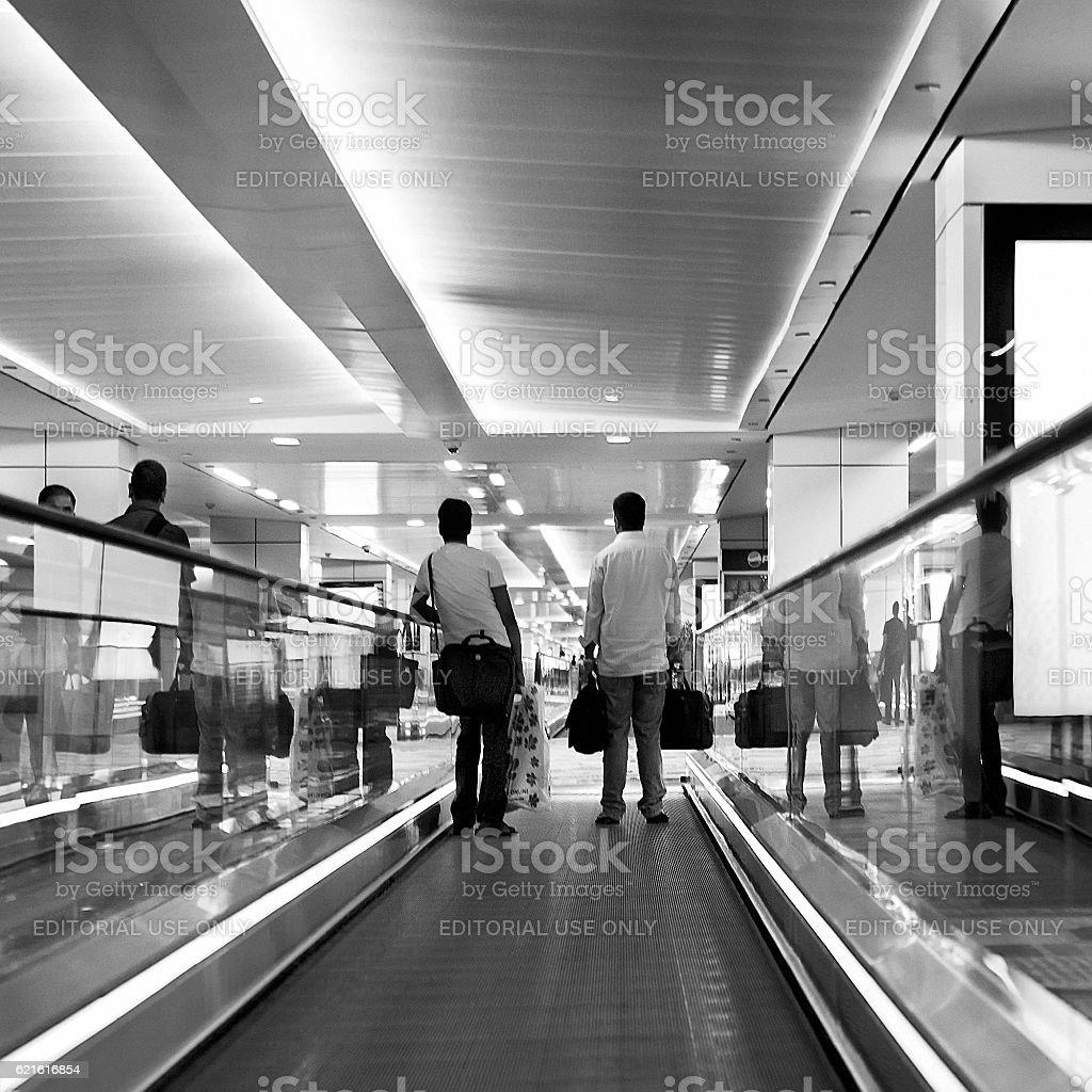 Passengers use travelator inside airport terminal stock photo