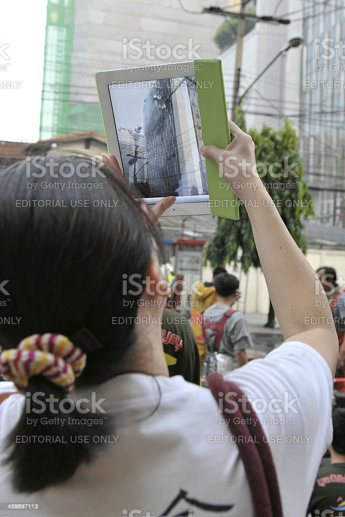 Passer-by Uses a Tablet Computer to Photograph an Office Fire royalty-free stock photo