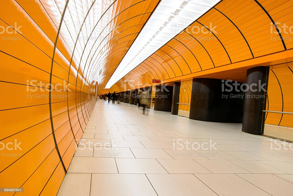 Passanten in einem orangen Tunnel stock photo