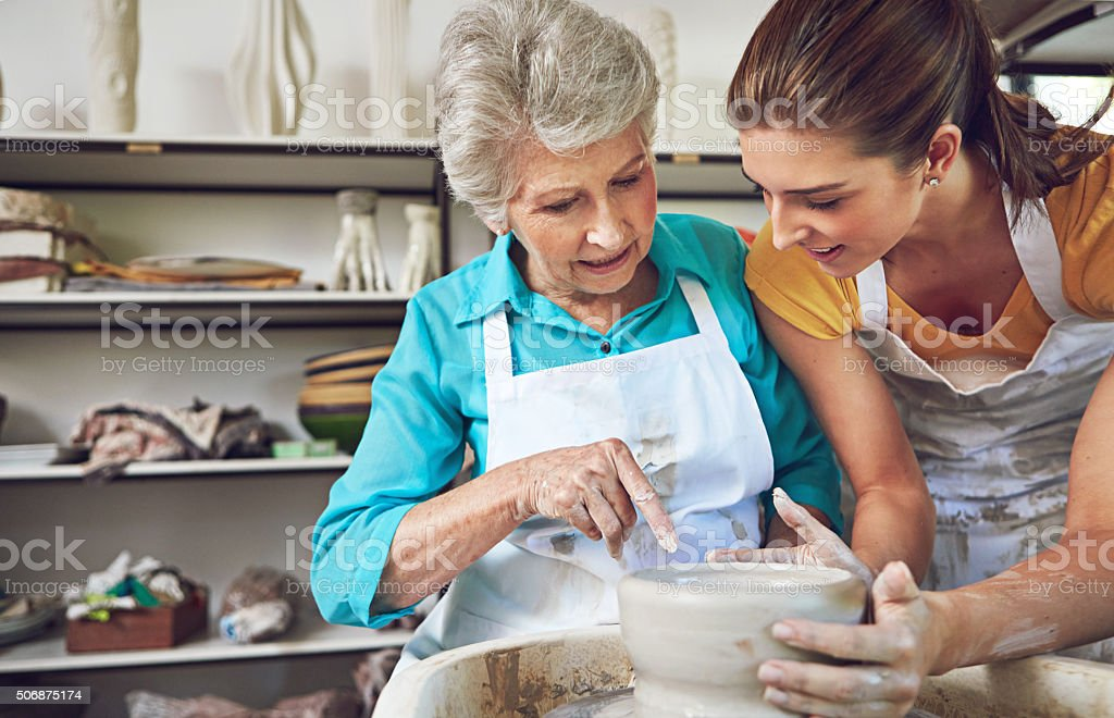 Passing on her pottery skills to Mom stock photo