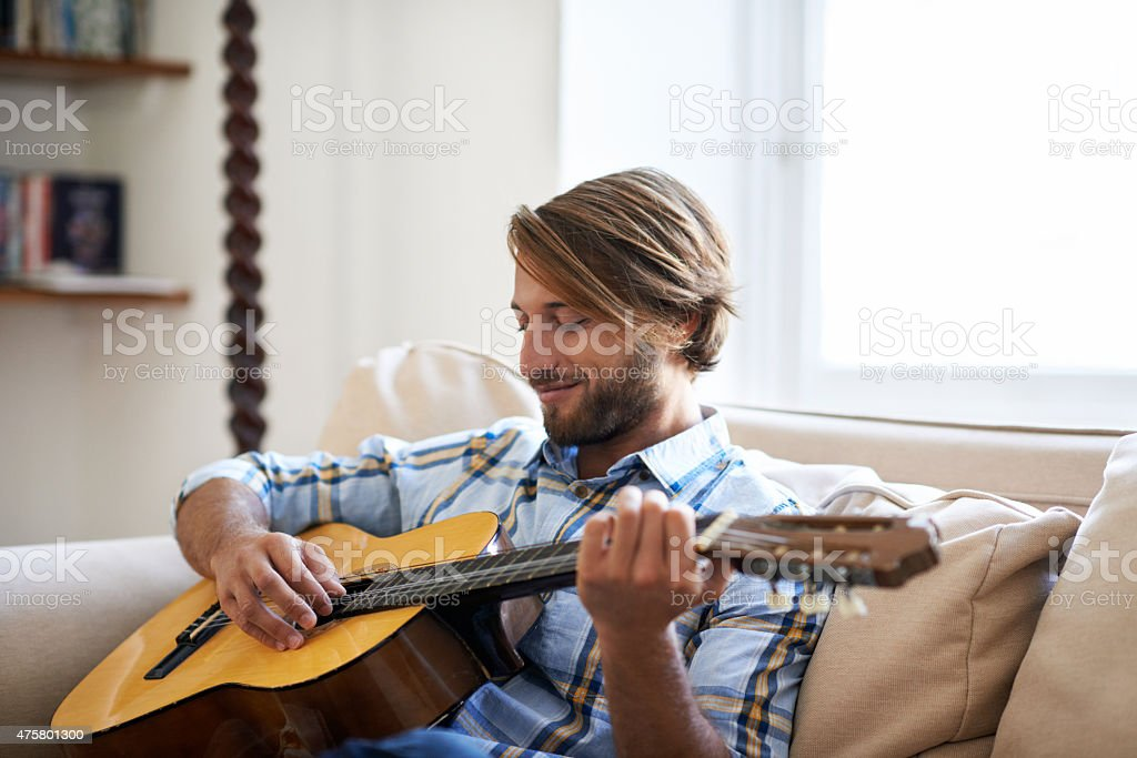 Passing the time with his guitar stock photo