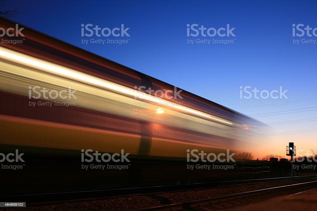 Passing train at sunset stock photo