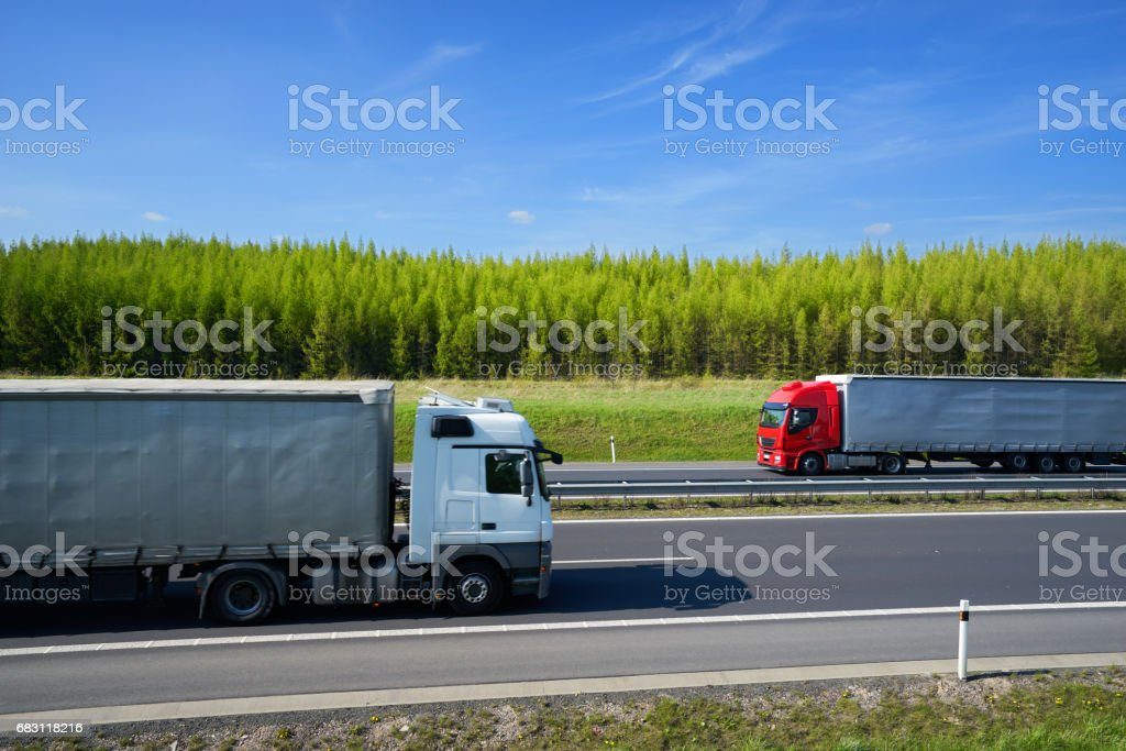 Passing trucks on a highway along a larch forest stock photo