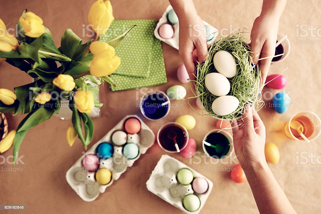 Passing unpainted eggs across the table stock photo