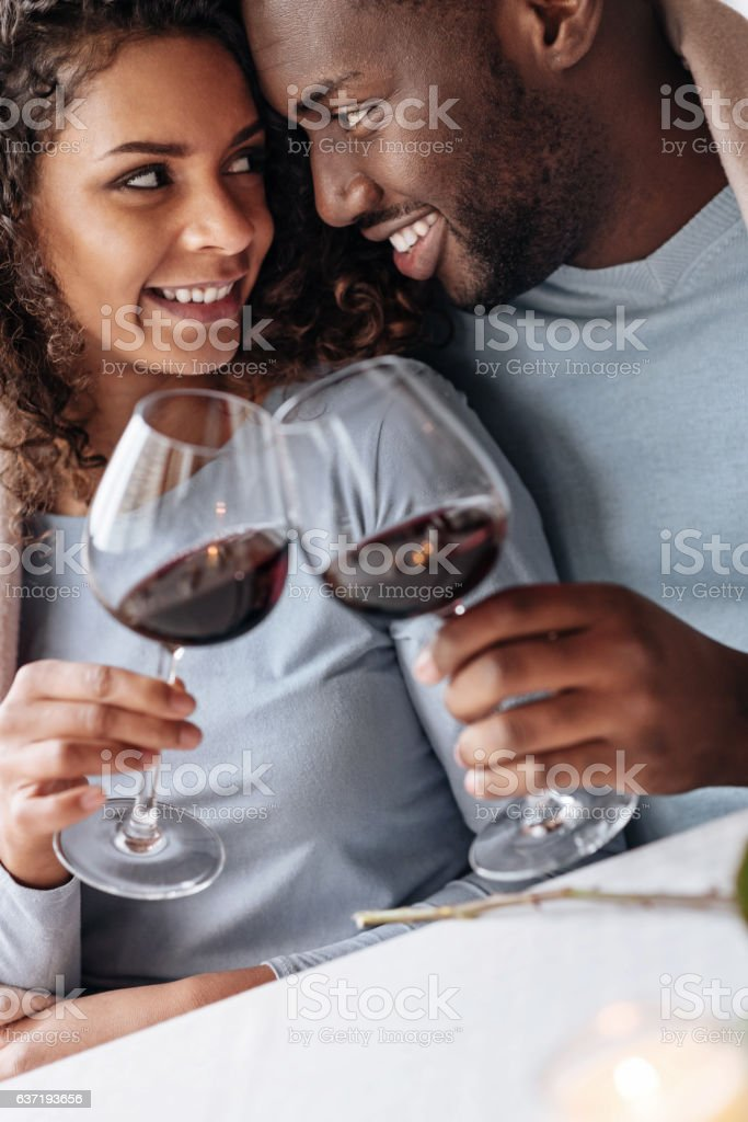 Passionate African American couple drinking wine in the restaurant stock photo