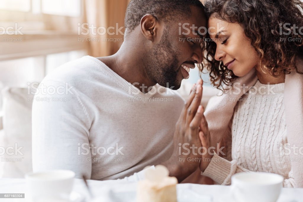 Passionate African American couple touching hands in the cafe stock photo