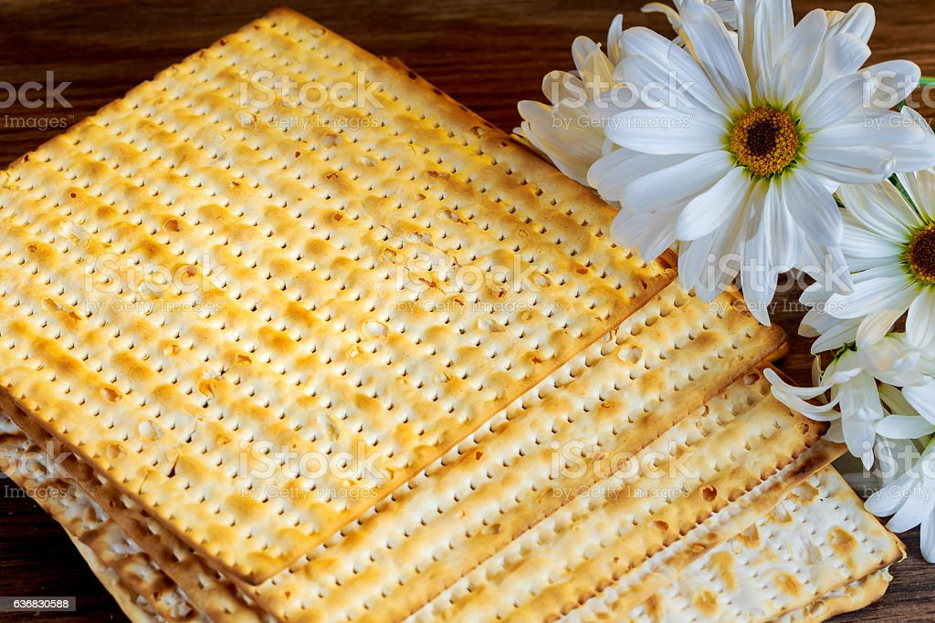 passover background. matzoh jewish holiday bread and flowers on gerbera stock photo