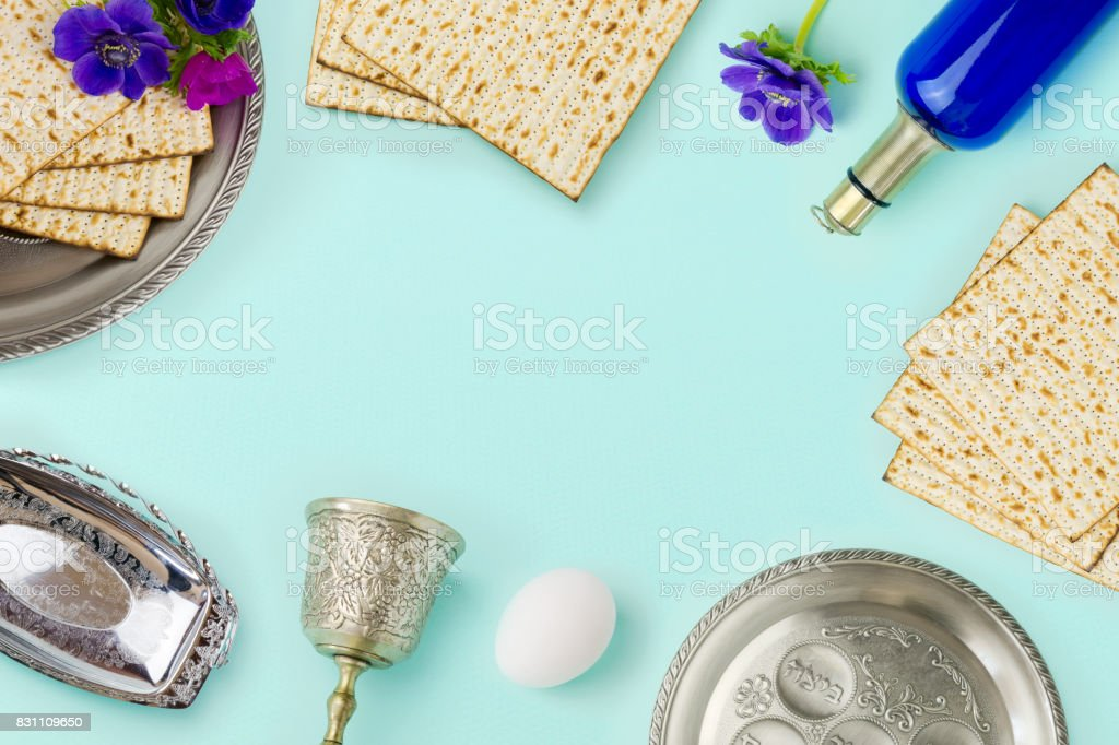 Passover holiday concept with wine bottle, matzoh and spring flowers over mint background with copy space. Top view from above stock photo