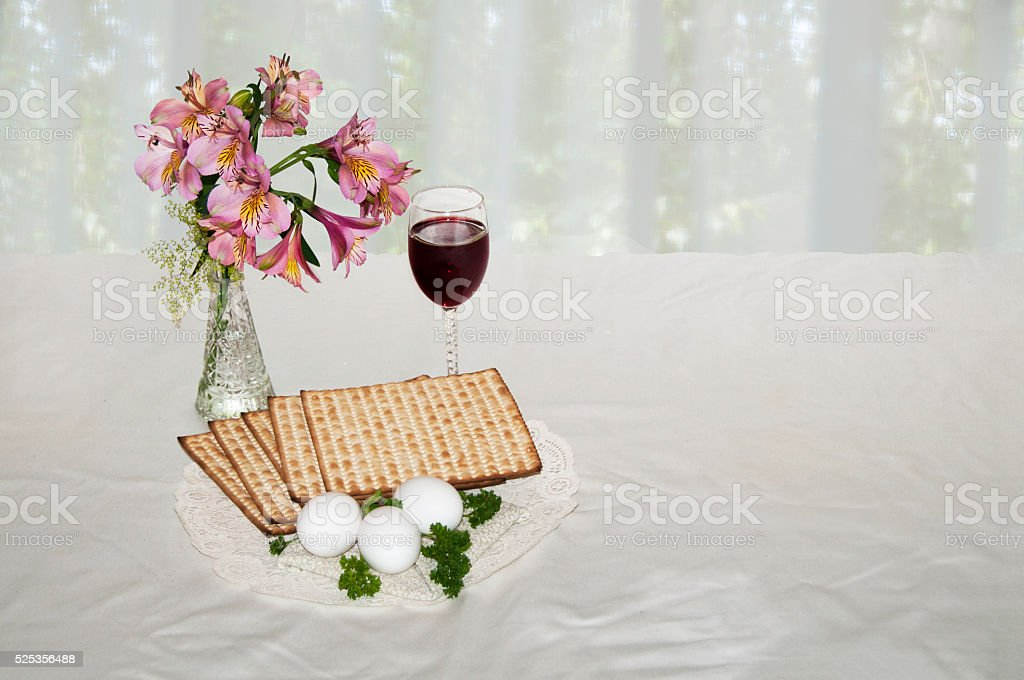 Passover matzo, wine, eggs, parseley and flowers stock photo
