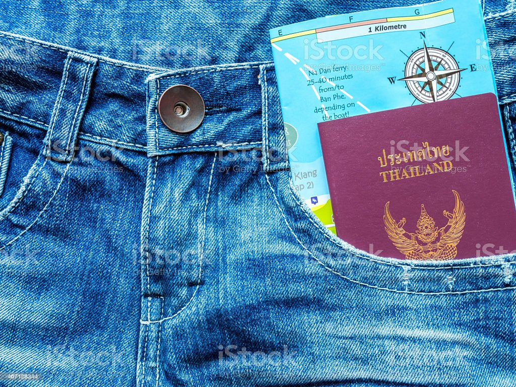 Passport book and map in blue jeans pocket/ traveling concept stock photo