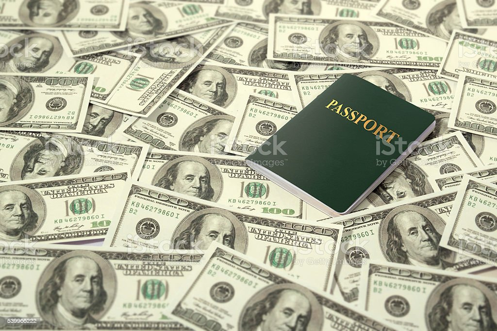 passport on dollars pile as background. stock photo