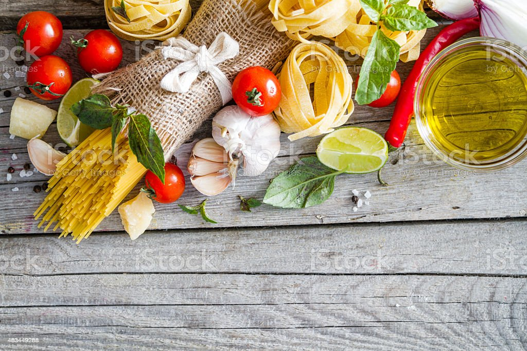 Pasta and ingredients - onion, tomato, basil, garlic, lemon stock photo