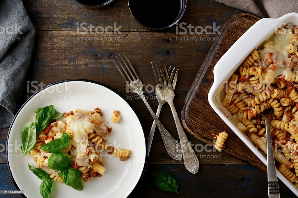 Pasta Bolognese with basil on plate and in baking dish stock photo