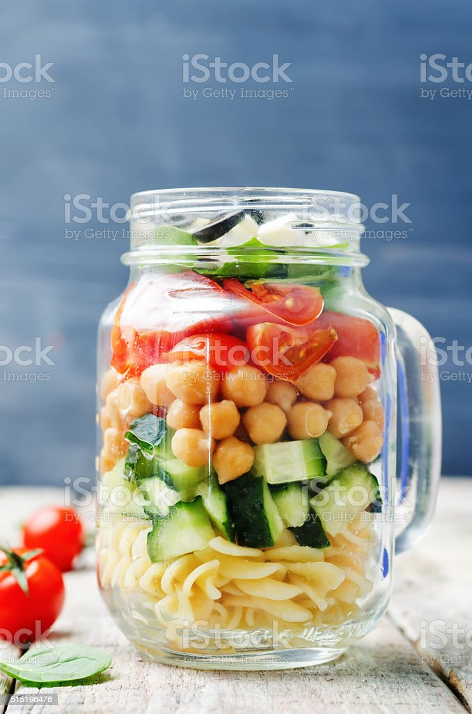 Pasta chickpeas cucumber tomatoes spinach goat cheese salad stock photo