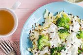 Pasta dish broccoli sauce sunflower seeds