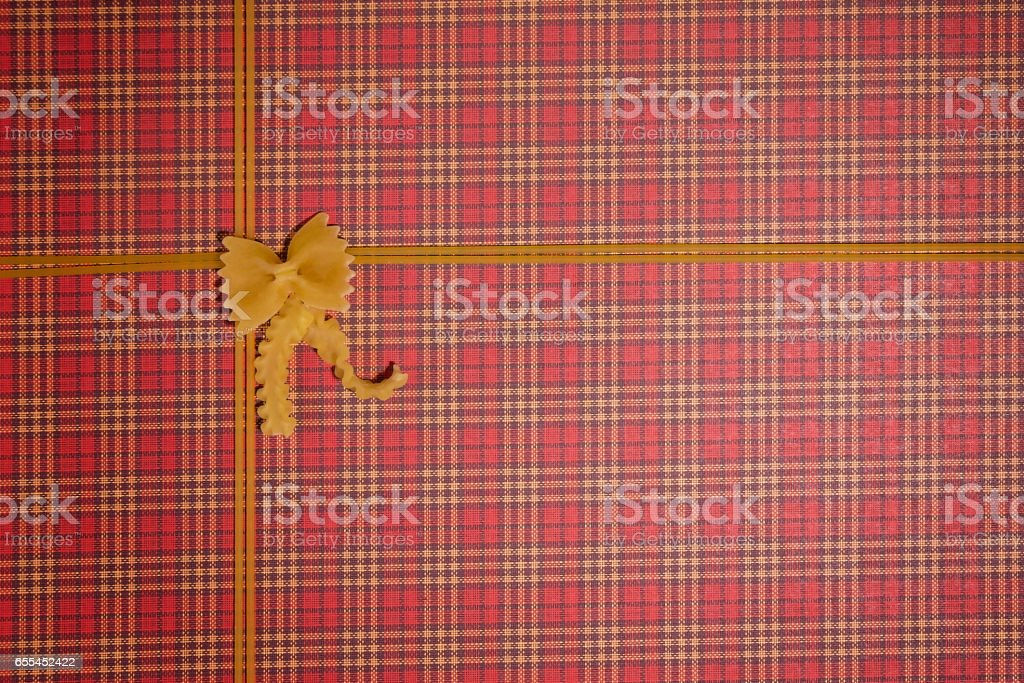 Pasta frame. Pasta in shape of bow with ribbon on red checkered background. Top view stock photo