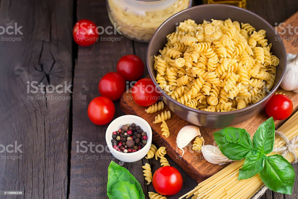 Pasta, herbsl and cherry tomatoes on old wooden background stock photo