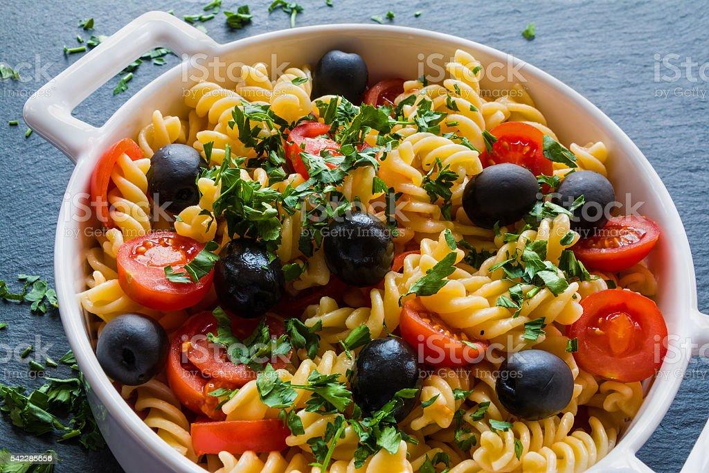 Pasta (fusilli) in white pan on black slate background stock photo