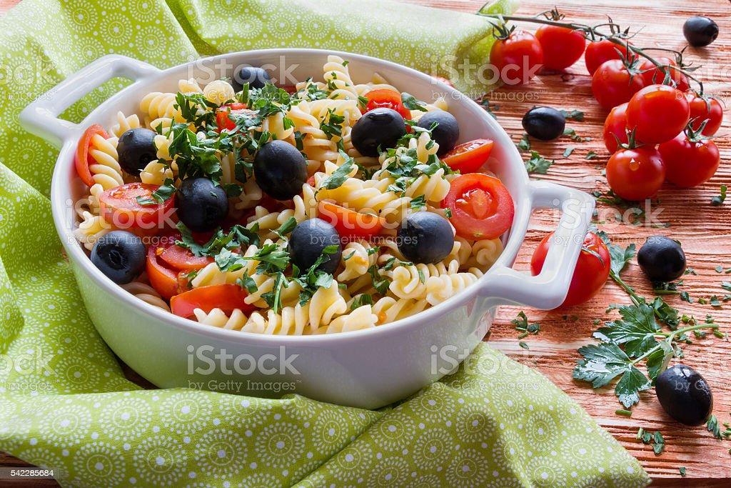 Pasta (fusilli) in white pan on wooden background stock photo