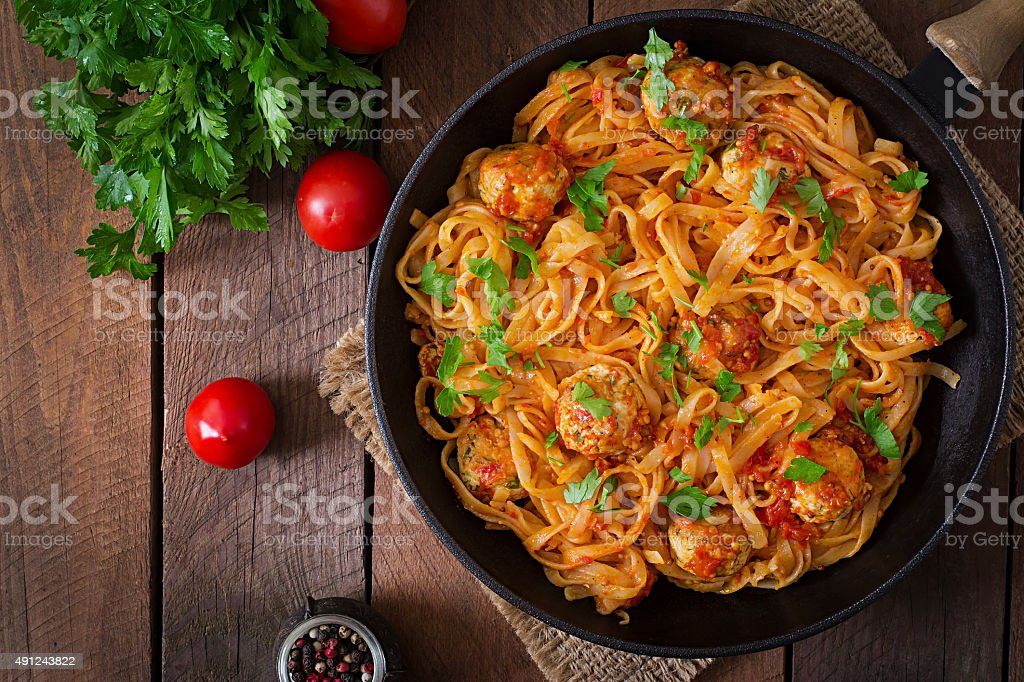 Pasta linguine with meatballs in tomato sauce. stock photo