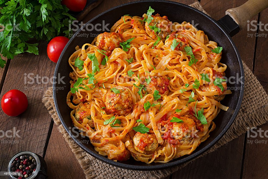 Pasta linguine with meatballs in tomato sauce. stock photo