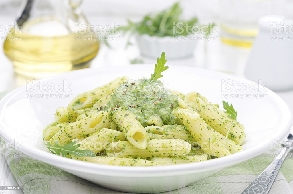 pasta penne with sauce of arugula and green peas close-up stock photo