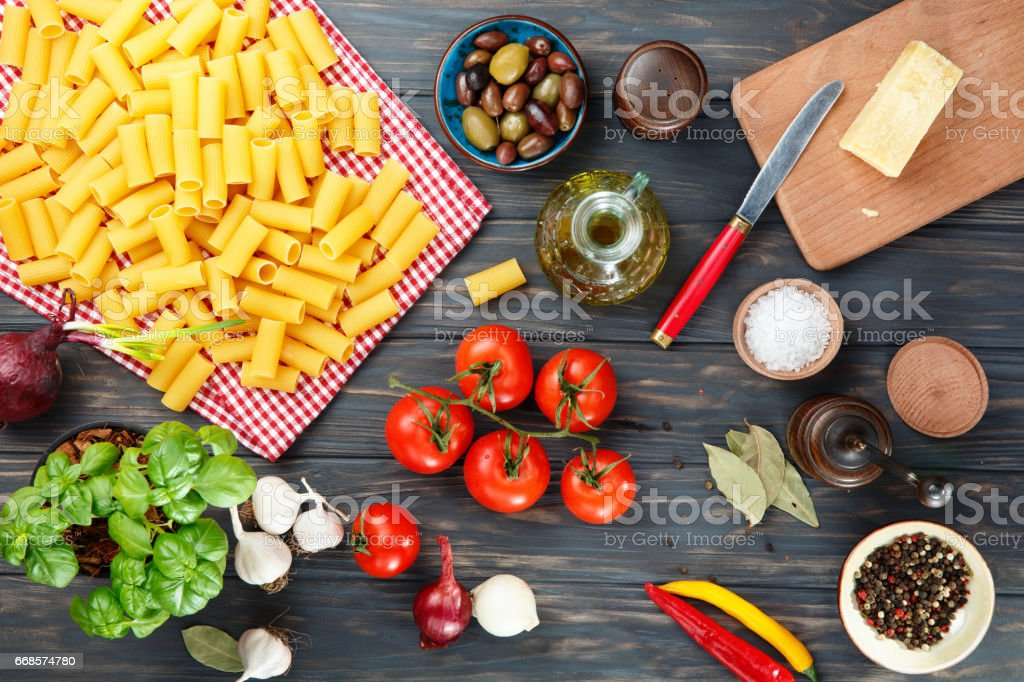 Pasta rigatoni with ingredients on wooden table, top view. stock photo