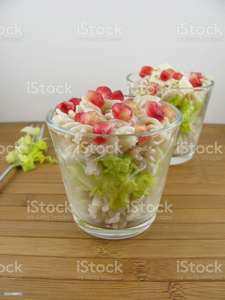 Pasta salad from spirelli pasta with pomegranate stock photo